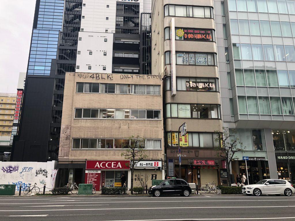 ①大阪メトロ四つ橋線『四ツ橋駅』の6番出口を出ると、このようなビルが見えます。右手側の路地に入ってください。